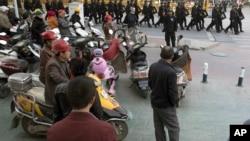 2017年11月5日,中部新疆地区的喀什市居民观看一队保安人员。