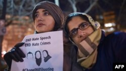 Women take part in a vigil for three young Muslims killed in Chapel Hill, North Carolina, at Dupont Circle in Washington, D.C., Feb. 12, 2015