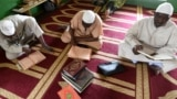 Les musulmans lisent un Coran après une prière du vendredi dans une mosquée d'Abidjan pendant le mois sacré du Ramadan, le 18 mai 2018