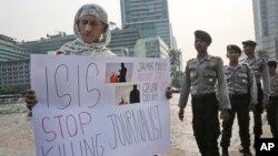 지난 5일 인도네시아 자카르타에서 경찰이 지켜보는 가운데, 한 남성이 테러단체 ISIL의 무고한 민간인 기자 살해를 규탄하는 시위를 하고 있다.. (자료사진)