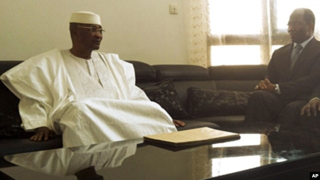 Mali's ousted President Amadou Toumani Toure (L) sits with Djibril Bassole, Burkina Faso's foreign minister and one of the leading mediators for West Africa's ECOWAS bloc, during a meeting in which Toure resigned in the capital Bamako, April 8, 2012.