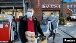 A man wearing a face mask carries a tobacco boxes after purchasing at the Macquenoise border post as France reopens its borders with its European neighbours after the lockdown to prevent the spread of the coronavirus disease (COVID-19) outbreak, in Macquenoise, Belgium June 15, 2