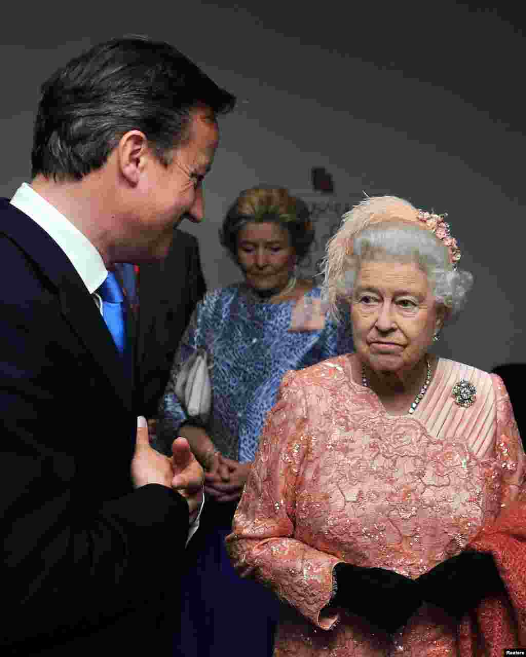 Britain's Queen Elizabeth (R) speaks to Prime Minister David Cameron as she arrives for the opening ceremony of the London 2012 Olympic Games at the Olympic Stadium July 27, 2012.