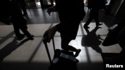 Passengers cast shadows as they walk along a terminal at Los Angeles International Airport in Los Angeles, California, March 4, 2013.