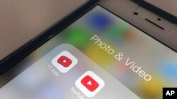 The YouTube app and YouTube Kids app are displayed on an iPhone in New York, April 25, 2018. YouTube is overhauling its kid-focused video app to give parents the option of letting humans, not computer algorithms, select what shows their children can watch