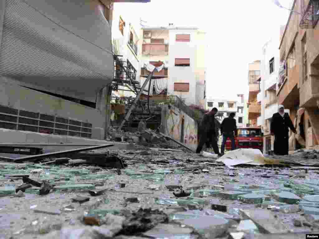 2012年11月26日,忠于叙利亚总统阿萨德的部队炮击了大马士革附近的达利亚之后,居民们走过破损建筑物的瓦砾残块。