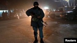 Police officer stands guard after arriving at site of Taliban suicide attack, Kabul, Nov. 27, 2014.