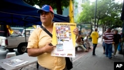 An activist of the opposition Justice First party holds a poster showing how to vote in congressional elections in Caracas, Venezuela, Nov. 26, 2015 — a day after Luis Diaz, a leader of the opposition Democratic Action party, was shot and killed.