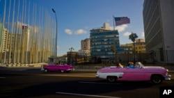 Wisatawan berkendara di mobil klasik Amerika dengan atap terbuka melintas di depan Kedubes AS, kanan, di Havana, Kuba, hari Kamis, 12 Januari 2017 (foto: AP Photo/Ramon Espinosa)