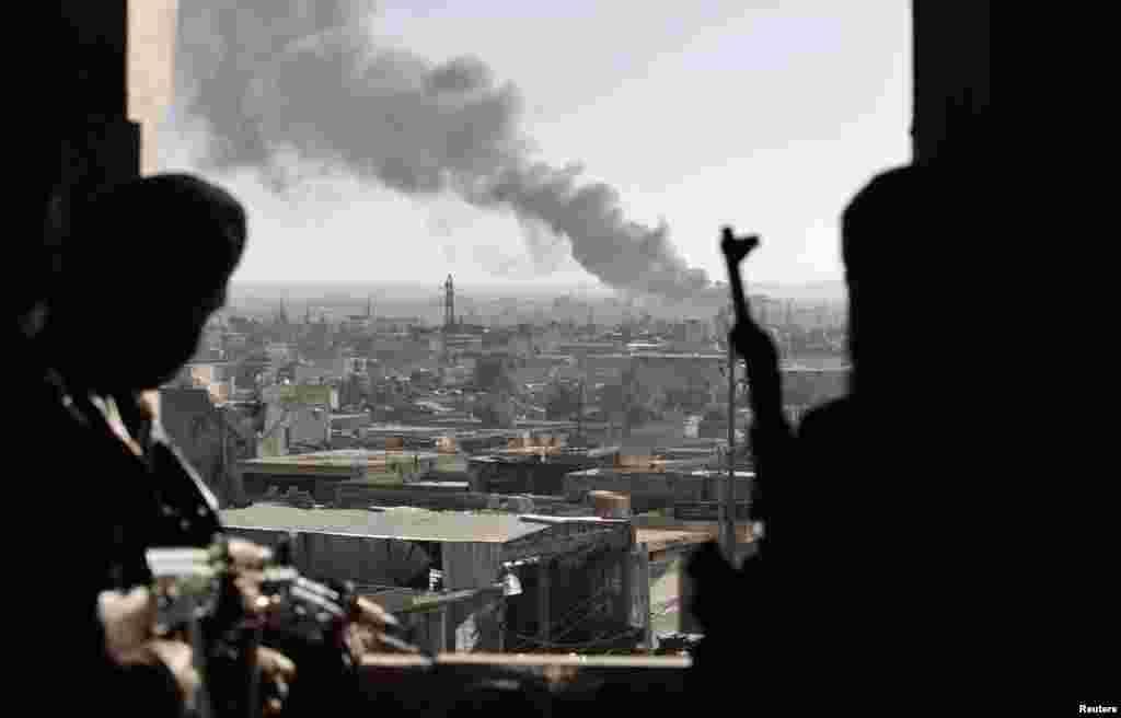 26일 시리아 정부군과 반군간 격돌이 있었던 알레포 지역에서 연기나는 곳을 바라보는 반군 병사들.