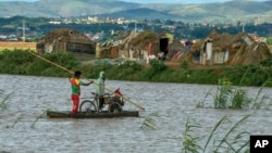 Residents cross flooded fields in Madagascar's capital Antananarivo, on Thursday, March 9, 2017.