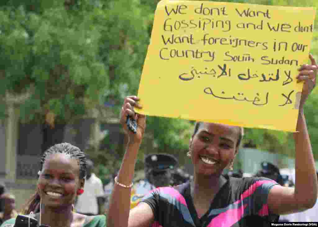 A woman holds up a hand-written sign at a government organized peace demonstration in Juba on March 10, 2014.
