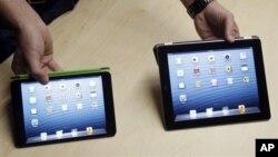 iPad Mini (kiri), dengan layar dua pertiga dan bobot setengah dari iPad generasi keempat. (AP/Marcio Jose Sanchez)