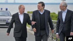 Russian President Vladimir Putin, left, European Commission President Jose Manuel Barroso, center, and European Council President Herman Van Rompuy walk during the Russia EU Summit outside St.Petersburg, Russia, Sunday, June 3, 2012.