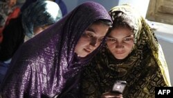Afghan women sit in a class and study using mobile phones in Kabul on November 3, 2012.