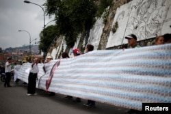 Demonstrators hold a banner made from three thousand two-bolivar-bills, that is equivalent approximately to $1 according to the black market exchange rate, in Caracas, Venezuela, June 10, 2017.