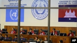 File photo of the Extraordinary Chambers in the Courts of Cambodia, court officers of the U.N.-backed war crimes tribunal are seen through windows during a hearing of former Khmer Rouge top leaders in Phnom Penh, file photo.