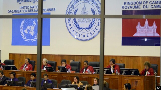 FILE - In this file photo released by the Extraordinary Chambers in the Courts of Cambodia, court officers of the U.N.-backed war crimes tribunal are seen through windows during a hearing of former Khmer Rouge top leaders in Phnom Penh, Cambodia.