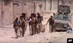 FILE - This frame grab from video released July 4, 2017, and provided by Furat FM, a Syrian Kurdish activist-run media group, shows U.S.-backed Syrian Democratic Forces fighters in the eastern side of Raqqa, Syria.