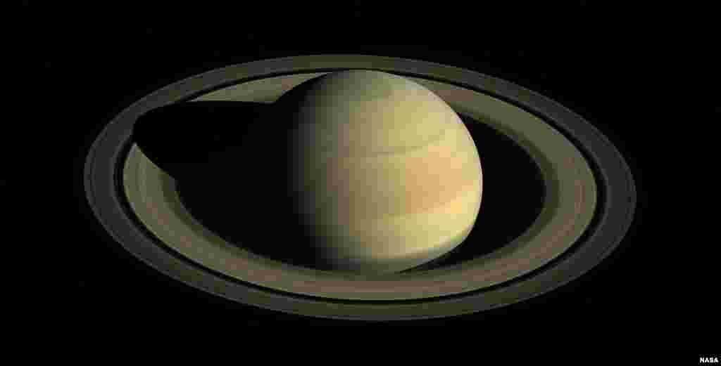 Foto tanggal 12 Agustus 2009, sebuah gambar campuran yang dirilis NASA menunjukkan Saturnus dalam posisi ekuinoks atau posisi di mana waktu siang hari dan malam hari sama yang terlihat dari pesawat luar angkasa Cassini yang sedang mendekat. Ekuinoks di Saturnus terjadi satu kali dalam 15 tahun waktu Bumi.