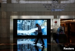 FILE - A man walks past screen at the Indonesia Stock Exchange building in Jakarta, Indonesia, Sept. 6, 2018.
