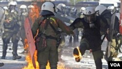 Pasukan keamanan Yunani memadamkan kebakaran akibat bom molotov yang dilemparkan para demonstran di Athena yang memrotes langkah-langkah penghematan (19/10).