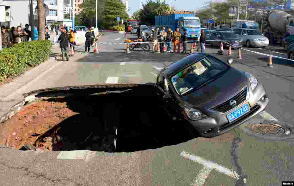 People look on as a car balances on the edge of a caved-in area on a street in Guangzhou, Guangdong province, China.