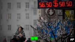 FILE - A woman passes a currency exchange in Moscow, Dec. 12, 2014.