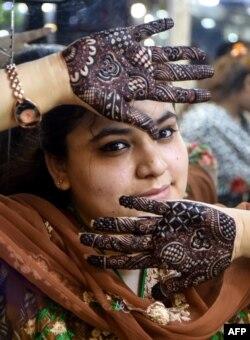 Perempuan Pakistan menunjukkan tangannya yang didekorasi henna untuk menyambut Idul Fitri.