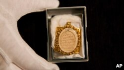 A lock of Wolfgang Amadeus Mozart's hair, contained in a 19th-century gilt locket is posed for photographs at the Sotheby's auction house in London, May 26, 2015.