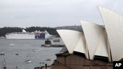 A cruise ship hangs a large national flag in celebration of Australia Day, in Sydney Harbour behind the Opera House in Sydney, Jan. 26, 2012.