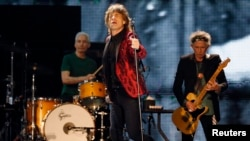 FILE - Mick Jagger (C), Charlie Watts (L) and Keith Richards of the Rolling Stones perform during a concert in Abu Dhabi, Feb. 21, 2014.
