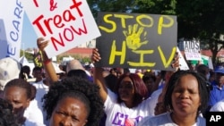FILE - Activists march in Durban, South Africa, July 18, 2016, at the start of the 21st World Aids Conference. A new clinical trial is underway in South Africa on an experimental vaccine that could safely prevent HIV, the virus that causes AIDS.