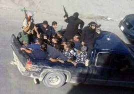 Gunmen drive away with about a dozen men, two in camouflage police uniforms, in Arsal, a Sunni Muslim town near the Syrian border in eastern Lebanon, Aug 2, 2014.