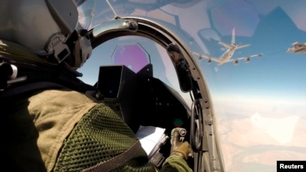 This remote camera screen grabs provided Friday, Sept.19, 2014 by the French Army's video and photo department ECPAD shows a Rafale jet fighter, partially seen at right, and a pilot fly over Iraq Friday.