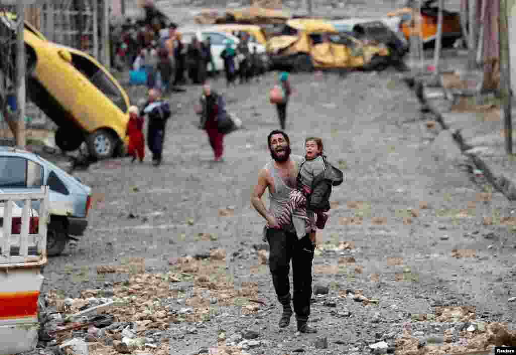 گریه یک مرد و دخترش که در حال فرار کردن از داعش در موصل عراق هستند.