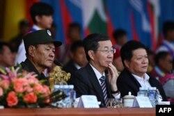 资料照片:佤邦联合军领袖鲍有祥(左)和中国外交部特使孙国祥(中)在缅甸佤邦观看庆祝与缅甸军队签署和平协议30周年的阅兵式。(2019年4月17日)