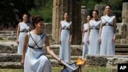 Une danseuse allume la flamme olympique dans l'Ancien Olympia, Grèce, jeudi 21 avril, 2016.