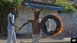 A supporter of Ivory Coast opposition leader Alassane Ouattara carry a burning tire during a protest in the city of Abidjan, Ivory Coast, Saturday, Dec. 4, 2010.