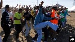 Les mineurs viennent commémorer la mémoire des mineurs de platine tués il y a un an alors qu'ils étaient en grève à Marikana , Afrique du Sud , le 16 août 2013.