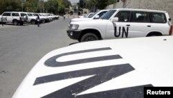 Xe của các quan sát viên quốc tế đậu trước một khách sạn ở Damascus