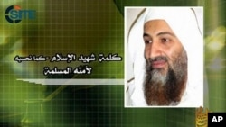 ຮູບນາຍ Osama bin Laden ຫົວໜ້າກຸ່ມກໍ່ການຮ້າຍອາລກາຍດາ ຈາກວີດີໂອຂອງອົງການ SITE ໃນລະຫວ່າງ ການຫຼິ້ນເທບສຽງຂອງນາຍ bin Laden ທີ່ພວກກໍ່ການຮ້າຍ ໄດ້ນຳອອກເຜີຍແຜ່ (18 ພຶດສະພາ 2001)