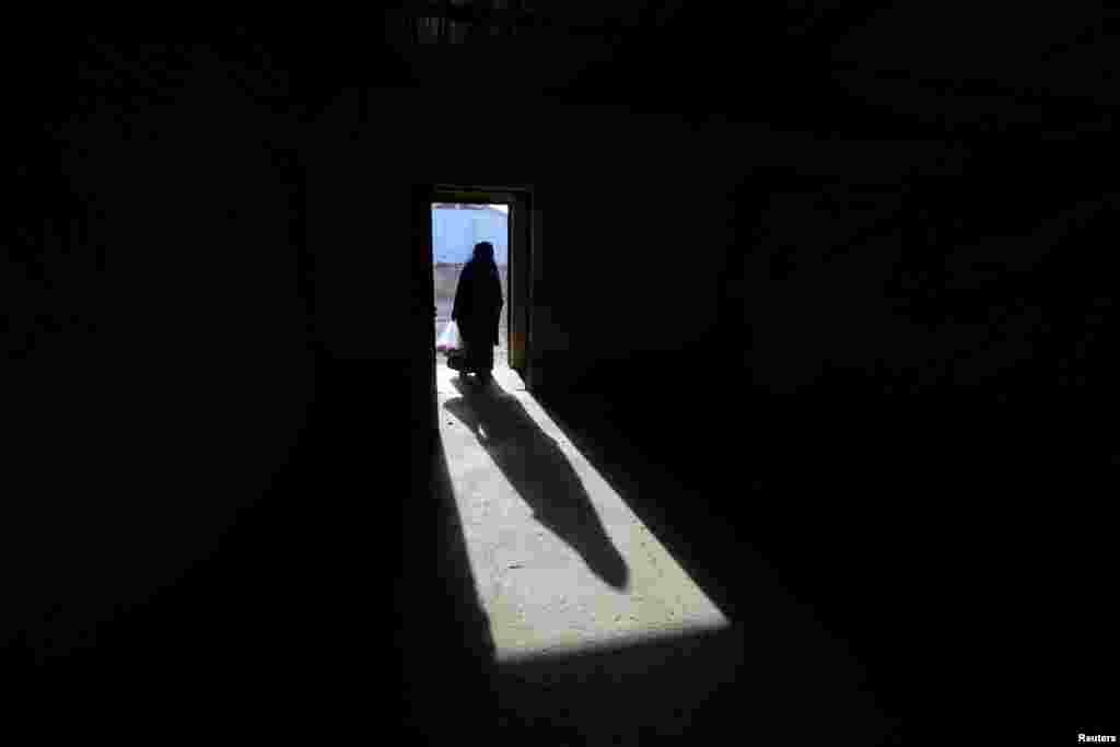 The shadow of a displaced old woman is seen in Hassan Sham camp, east of Mosul, Iraq.