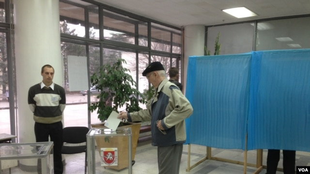 A man casts his ballot at a polling station during the Crimean referendum, in Simferopol, Ukraine, Sunday, March 16, 2014. (VOA/E. Arrott).