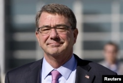 FILE - U.S. Defense Secretary Ash Carter walks on the tarmac before boarding his plane at Queen Alia Airport in Amman, Jordan, July 24, 2015.