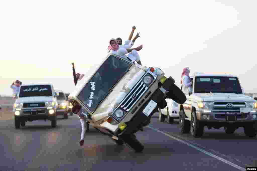 Remaja-remaja Saudi mendemonstrasikan kemahiran mengendarai mobil dengan 2 ban di kota Tabuk, Saudi Arabia.