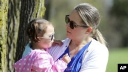 FILE - In this April 23, 2019 photo, Lisa Kum is seen in a park near Madison, Wis., with her daughter Emma, 2. In 2014, Kums husband Sothy Kum allowed an acquaintance to pay him to send marijuana to his house.