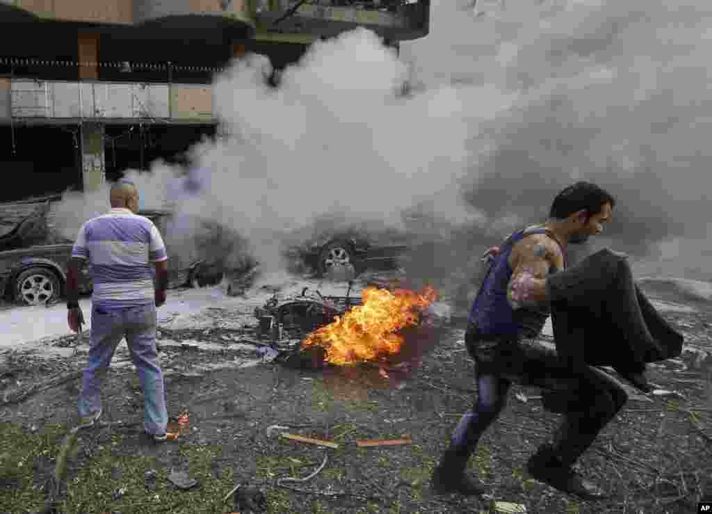 A Lebanese man runs in front of a burned car, at the scene of two explosions near the Iranian Embassy in Beirut, Lebanon. The blasts in south Beirut's neighborhood of Janah killed more than 20 people and caused extensive damage on the nearby buildings and the Iranian mission.