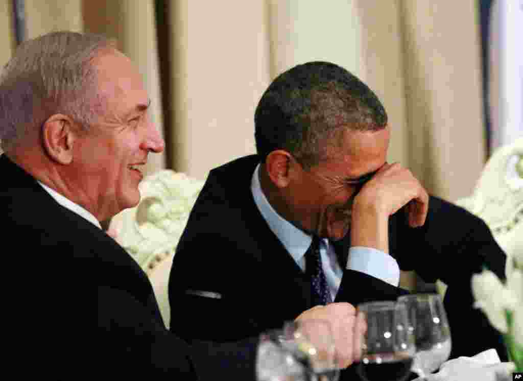 Obama shares a laugh with Israel's Prime Minister Benjamin Netanyahu, during an official state dinner hosted by Israel's President Shimon Peres (not pictured) in Jerusalem, March 21, 2013.