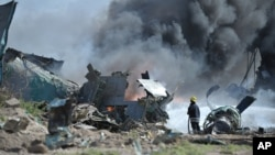FILE - African Union Mission in Somalia soldiers attempt to extinguish the fire at the site of an airplane crash in Mogadishu, Somalia. (AMISOM)